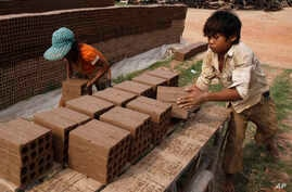 Cambodian children prepare bricks to dry under the sun light at a brick factory in Chheuteal village, Kandal province, some 27…