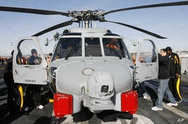 Players from Arizona State and Texas look over a navy MH-60R Seahawk helicopter during a tour of the USS Ronald Reagan aircraft…