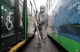 A worker wearing a protective suit sprays disinfectant as a precaution against the coronavirus at a bus garage in Seoul, South…