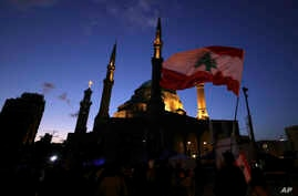 Anti-government protesters wave Lebanese flags and chant slogans, during ongoing protests against the Lebanese government, in…