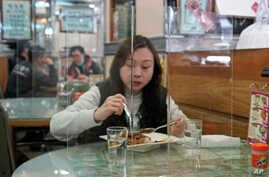 Customer has lunch with a transparent plastic panel setup on the table to isolate her from others in hopes of stopping the…