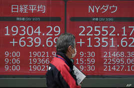 A man walks past an electronic stock board showing Japan's Nikkei 225 and New York Dow index at a securities firm in Tokyo…