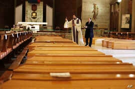 Don Marcello Crotti, left, blesses the coffins with Don Mario Carminati in the San Giuseppe church in Seriate, Italy, Saturday,…
