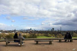 People sit on benches at Primrose Hill, in London, Sunday, March 29, 2020. The public have been asked to self isolate, keeping…
