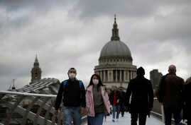 People wearing face masks walk across the Millennium footbridge backdropped by the dome of St Paul's Cathedral in London,…