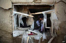 FILE- in this Dec. 11, 2019, photo, a boy inspect his damaged home after after an attack near the Bagram Air Base In Parwan…