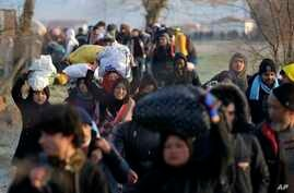 Migrants walk to reach Pazarakule border gate, Edirne, Turkey, at the Turkish-Greek border on Sunday, March 1, 2020. Turkey's…