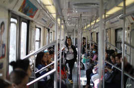 Commuters ride in a subway car in the section dedicated to women and children under 12, in Mexico City, Thursday, March 5, 2020…