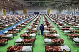 People in protective clothing walk past rows of beds at a temporary 2,000-bed hospital for COVID-19 coronavirus patients set up…