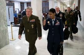 U.S. Marine Corps Gen. Kenneth McKenzie, Jr., Commander, U.S. Central Command, left, walks to a House Armed Services hearing,…