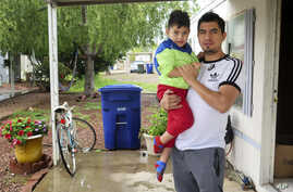 Osvaldo Salas, 29, stands with his son outside their home in suburban Phoenix on Wednesday, March 18, 2020. Salas, who isn't…