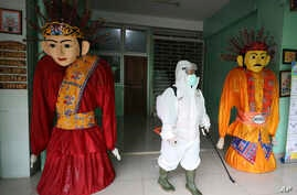 "A member of the Red Cross wears a protective suit past traditional giant characters called ""ondel-ondel' as she and her team…"