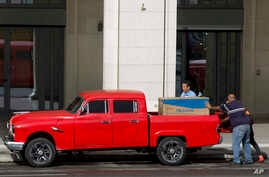 Men load up a newly bought refrigerator onto a truck in Havana, Cuba, Monday, March 9, 2020. In recent months, Cuban…