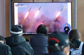 People watch a TV showing file images of North Korea's missile launch during a news program at the Seoul Railway Station in…