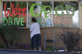 Lucy Kwak paints a sign on the window of a fast food chain's restaurant indicating that the drive-thru window is still open as…
