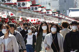 Visitors wearing face masks walk through Nakamise alley at Asakusa in Tokyo, Friday, March 20, 2020. For most people, the new…