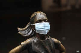"A surgical mask is placed on The ""Fearless Girl"" statue outside the New York Stock Exchange on Thursday, March 19, 2020, in New…"