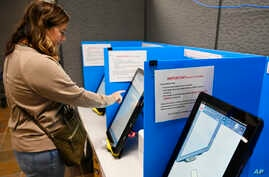 FILE-In this Tuesday, Nov. 5, 2019 file photoCourtney Parker votes on a new voting machine, in Dallas, Ga. Election integrity…