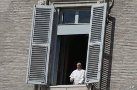 Pope Francis leans out of his studio window overlooking St. Peter's Square at the Vatican, Sunday March 15, 2020. For most…