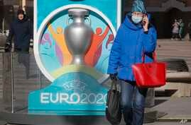 A woman wears a medical mask walks past a sign with Euro 2020 emblem in St.Petersburg where UEFA planned to host four UEFA EURO…