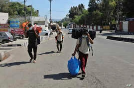 Indian students returning from Uttar Pradesh amid Coronavirus concerns walk after arriving at a railway station in Jammu, India…