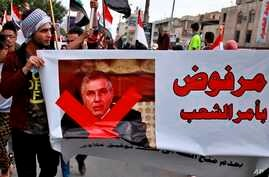 """Protesters hold a poster showing Iraq's Prime Minister-designate Mohammed Tawfiq Allawi with Arabic that reads, """"Rejected by…"""