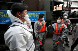 South Korean soldiers wearing protective gears talk each others as they disinfects on the street as a precaution against the…