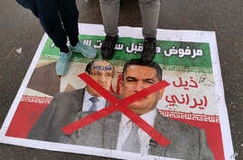 Anti-government protesters stand on a defaced poster with pictures of former Iraqi Prime Minister Nouri al-Maliki, left, and…
