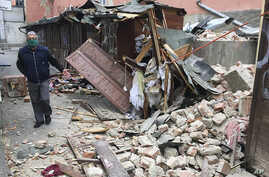 A man inspects the damage caused by an earthquake in Zagreb, Croatia, Sunday, March 22, 2020. A strong earthquake shook Croatia…