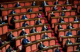 Senators, most wearing face masks, listen as Italian premier Giuseppe Conte informs them on coronavirus situation, in Rome,…