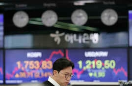 A currency trader watches the computer monitors near the screens showing the Korea Composite Stock Price Index (KOSPI), left,…