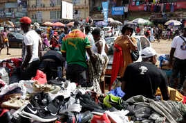 Pedestrians shop for clothes at Mokolo Market in Yaounde, Cameroon, Thursday Oct. 11, 2018. Cameroon continues to wait for…