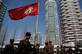 FILE - In this April 13, 2017, file photo, North Korean soldiers carry the Korean People's Army flag as they walk past…