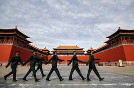 Soldiers wearing protective face masks march past the closed entrance gates to the Forbidden City, usually crowded with…