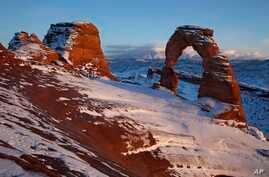 Delicate Arch glows in light from the setting sun as alpenglow lights up the La Sal mountains in the distance Friday, Dec. 31,…