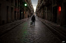 A man walks along an empty street in downtown Barcelona, Spain, Thursday, March 26, 2020 as the lockdown to combat the spread…