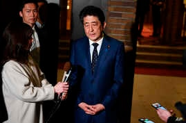 Japan's Prime Minister Shinzo Abe talks to journalists in front of the prime minister's residence in Tokyo, Tuesday, March 24,…