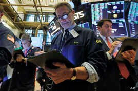 Trader Ronald Madarasz, center, works on the floor of the New York Stock Exchange, Tuesday, March 10, 2020. Stocks, Treasury…