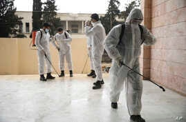 Members of a humanitarian aid agency disinfect Ibn Sina hospital as prevention against coronavirus in the city of Idlib, Syria,…
