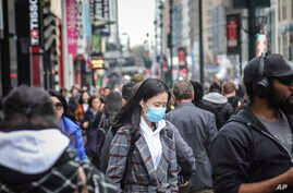 A pedestrian wears a surgical mask on a busy street in mid-town Manhattan, as concerns grow around COVID-19, Tuesday March 3,…