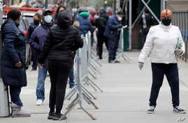 People stand in line as they wait to get tested for COVID-19 at a just-opened testing center in the Harlem section of New York,…