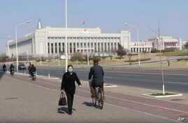 People walk past the building of the Presidium of the Supreme People's Assembly in Pyongyang, Thursday, April 9, 2020. North…