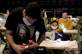 Volunteers wearing face masks to curb the spread of the new coronavirus, sew face masks for poor people, at the Hafez theatre…