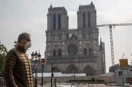 A man wears a mask to protect against the spread of the coronavirus as he walks past the Notre Dame cathedral in Paris, Monday,…