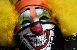 A clown wearing a protective face mask as a precaution against the spread of the new coronavirus, attends a protest in Mexico…