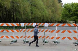 In this photo taken Wednesday, April 15, 2020, a woman jogs past a barricade outside a park in Salem, Ore. Oregon is in its…