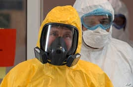 FILE - In this file photo taken on Tuesday, March 24, 2020, Russian President Vladimir Putin wearing a protective suit enters a…