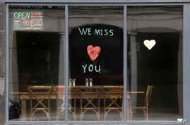 A message is posted on the front window of the Ranging Bull Saloon which remains closed during the coronavirus pandemic,…