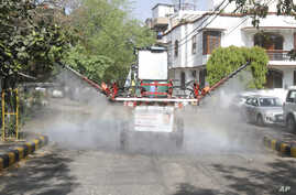 A Delhi government worker sanitizes a residential area using a Japanese machinery capable of disinfecting a large area to…