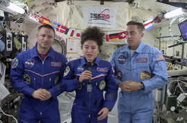 In this image from video made available by NASA, U.S. astronaut Jessica Meir speaks, accompanied by Andrew Morgan and Chris…